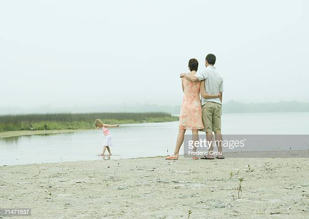 Family at the beach, parents watching little girl play in water