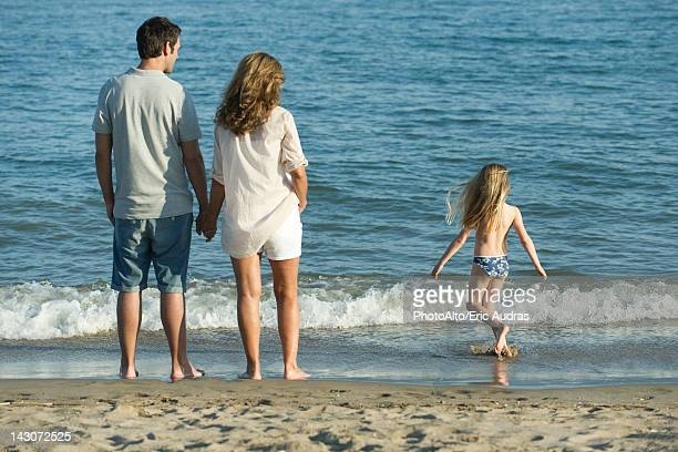 Family at the beach, rear view