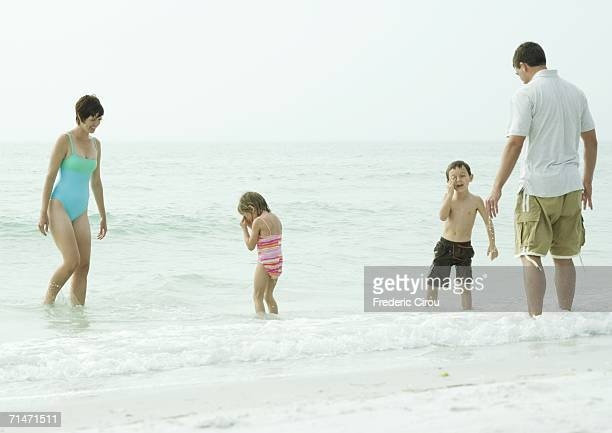 Family at the beach, standing in water