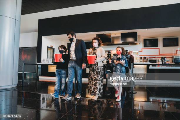 family at the movie theater bar is buying popcorn - film industry stock pictures, royalty-free photos & images