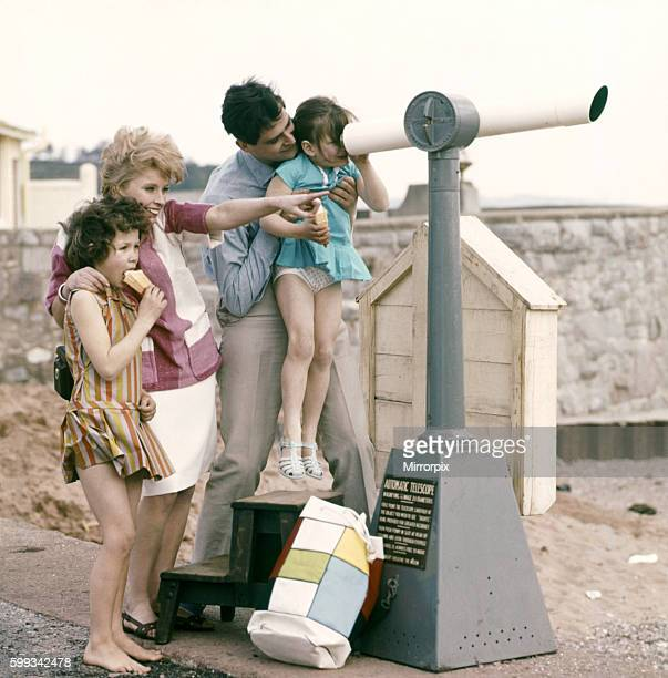 A family at the seaside loking through a telescope out to sea from the shore Circa 1960