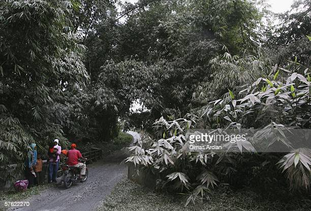 A family await public transport in Telogolele village which is aftected by Mount Merapi ash on May 16 2006 near the tourist destination city of...