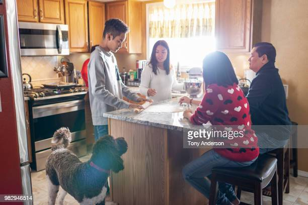 Family baking together in home kitchen with their dog watching