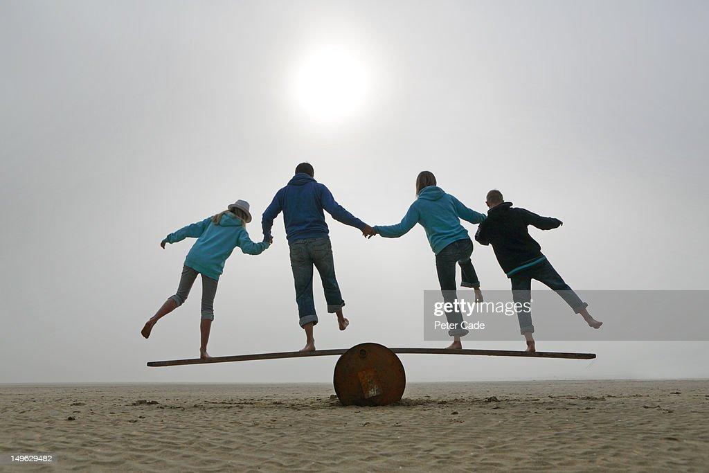 family balancing on beach : Stock Photo