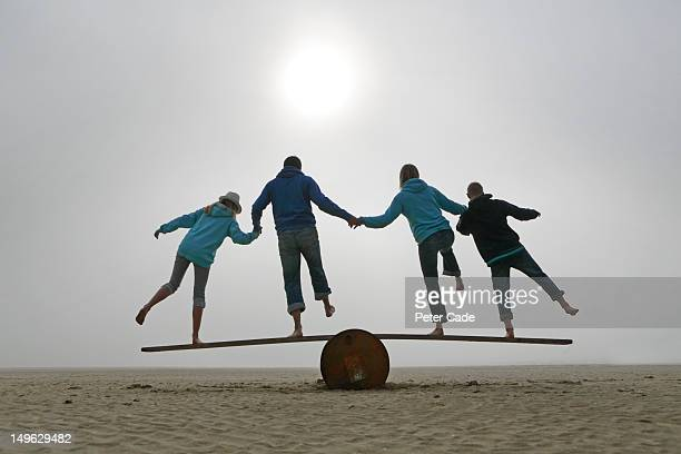 family balancing on beach