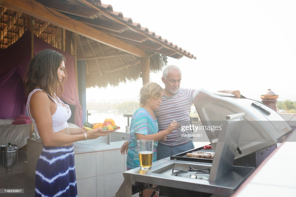 Family barbecue with older man, young woman and girl on a penthouse terrace : Stock Photo