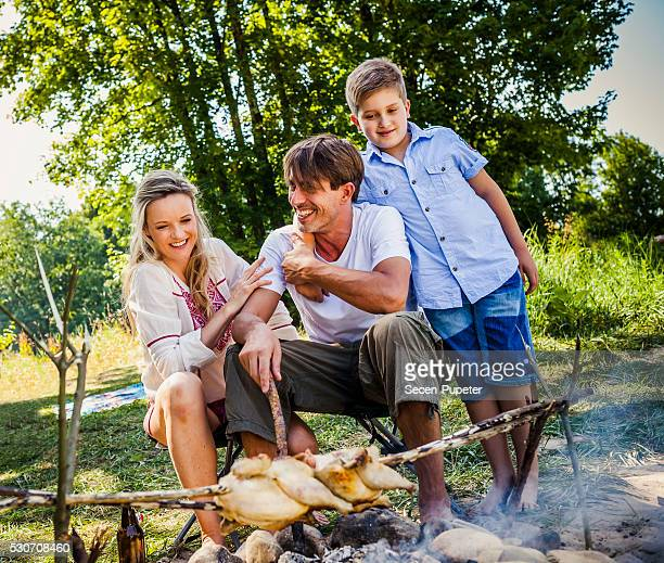 Family barbecuing on the riverside, foothills of the Alps, Bavaria, Germany
