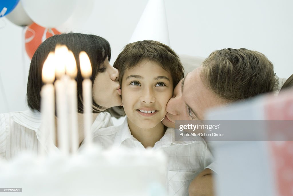 Family behind birthday cake with lit candles, parents kissing boy on cheeks : Stock Photo