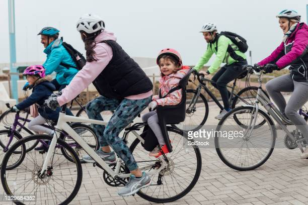 family bike ride at the coast - headwear stock pictures, royalty-free photos & images