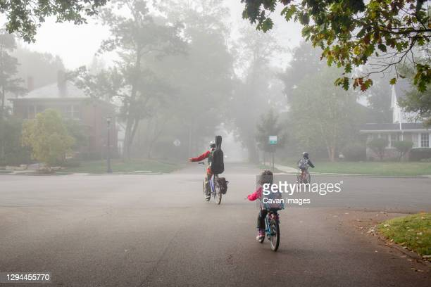 a family bikes to school together on foggy street with backpacks on - wrong way stock pictures, royalty-free photos & images