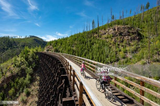 family biking at the myra canyon trestles near kelowna - kelowna stock pictures, royalty-free photos & images