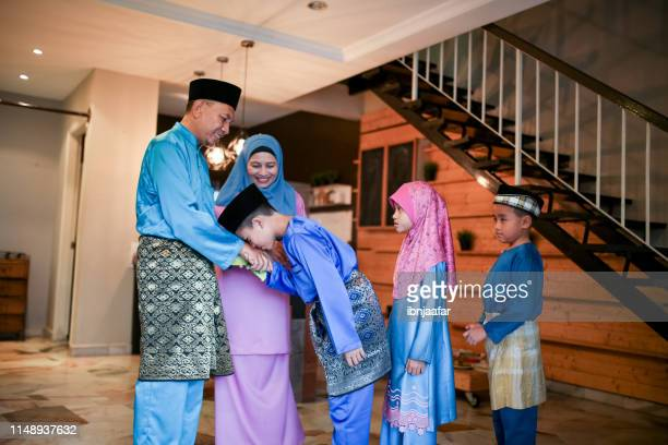 family blessing during eid celebration - eid al adha stock pictures, royalty-free photos & images