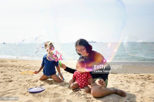 Family blowing bubbles on a beach