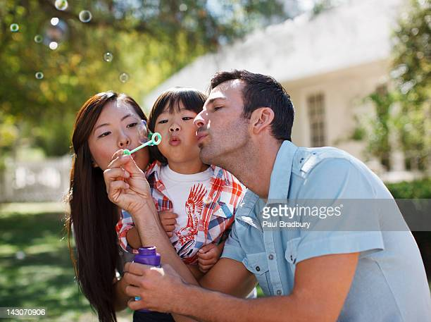 family blowing bubbles together outdoors - östasiatiskt ursprung bildbanksfoton och bilder