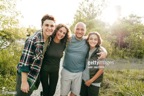 family bonding and having a fun time together. siblings and parents embracing and smiling at the camera. - four people stock pictures, royalty-free photos & images