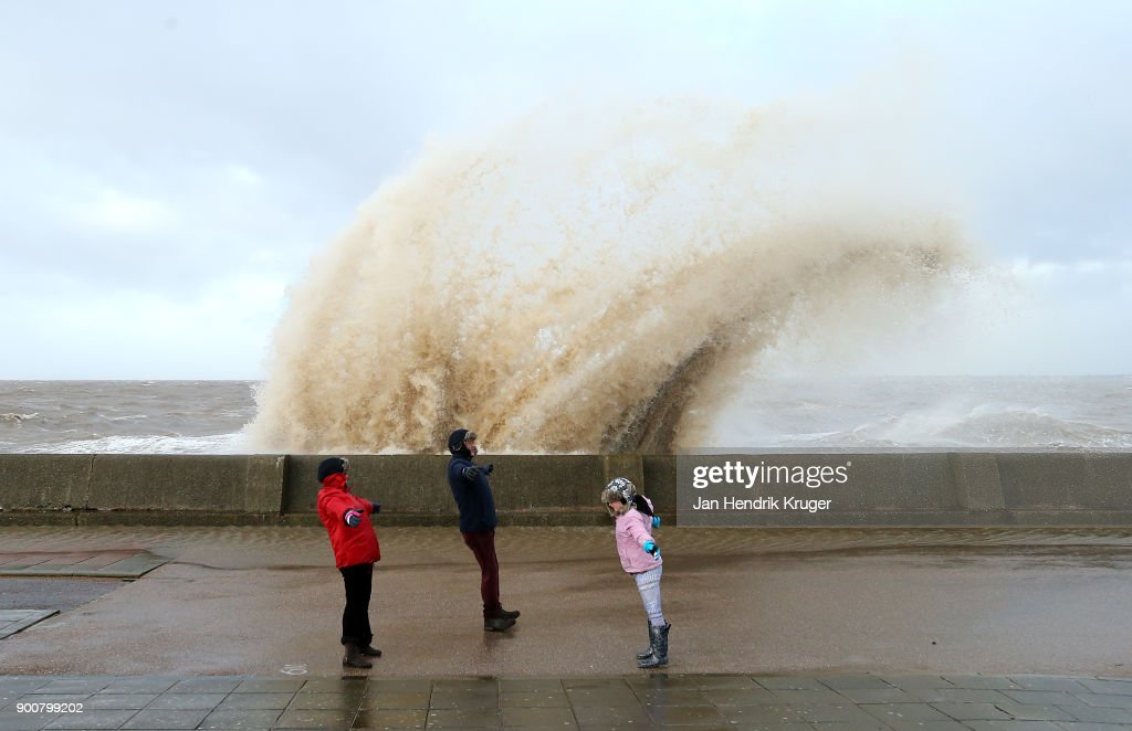 A family brave strong winds as waves crash over the tidal wall on New Brighton Promenade on January 03, 2018 in New Brighton, United Kingdom. A yellow warning is in place as Storm Eleanor brings winds of up to 100mph to parts of the UK and Ireland.