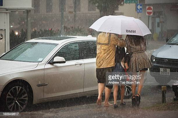 Family braves a typical afternoon thunderstorm in Tiong Bahru, Singapore. The father is barefooted, the mother in high heels, their daughter in...
