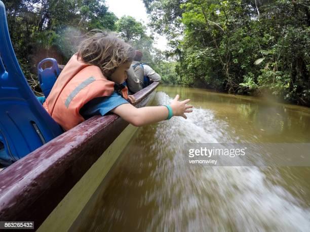 family braves the amazon jungle in a boat - saggezza foto e immagini stock
