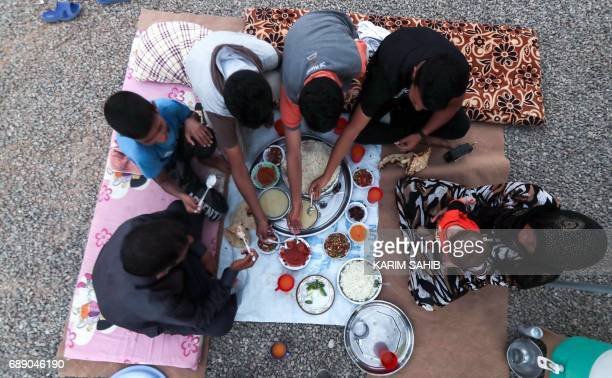TOPSHOT A family breaks their fast on the first day of the Muslim holy month of Ramadan at alKhazir camp for the internally displaced located between...