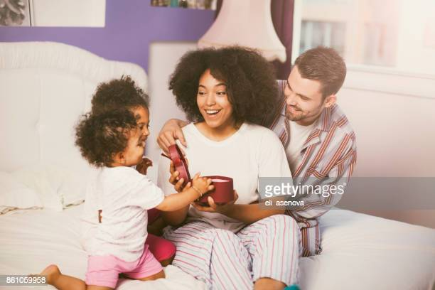 family bringing mother presents in bed - mother's day stock pictures, royalty-free photos & images