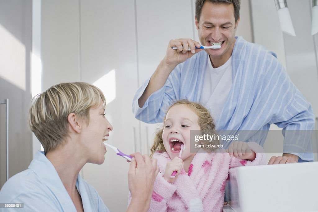 Family brushing teeth together : Stock Photo