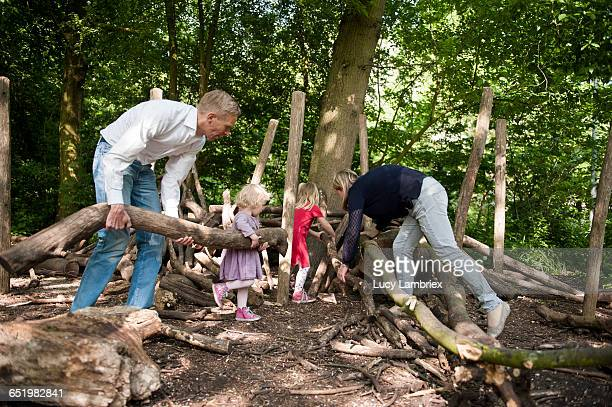 Family building a hut with logs