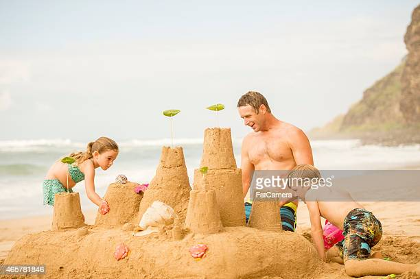Family building a sandcastle on the beach in Hawaii