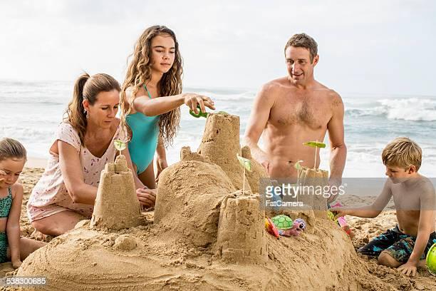 Family building a sandcastle on the beach in Hawaii