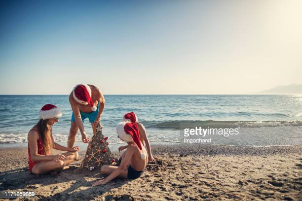 family building and decorating sand christmas tree on beach - beach christmas stock pictures, royalty-free photos & images