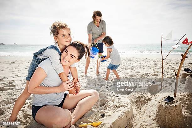 Family building sandcastle on beach