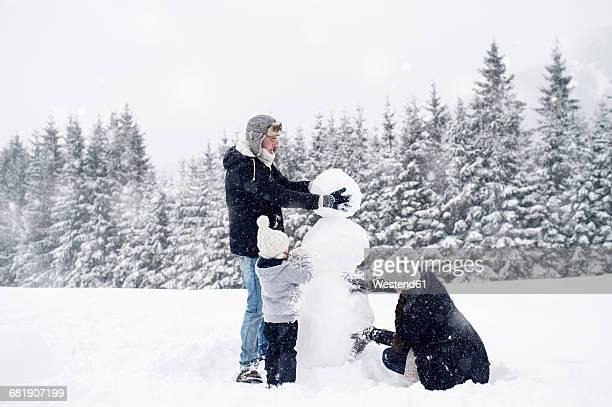 family building snowman together - bonhomme de neige photos et images de collection