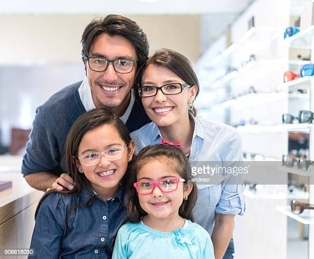 family buying glasses at the optician's shop - occhiali da vista foto e immagini stock