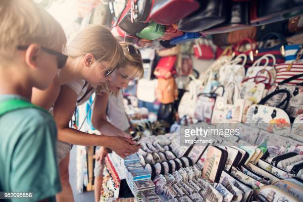 Family buying souvenirs at street market in Pisa