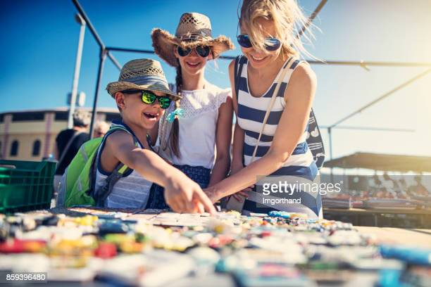 family buying souvenirs on flea market in andalusia, spain - souvenir stock pictures, royalty-free photos & images