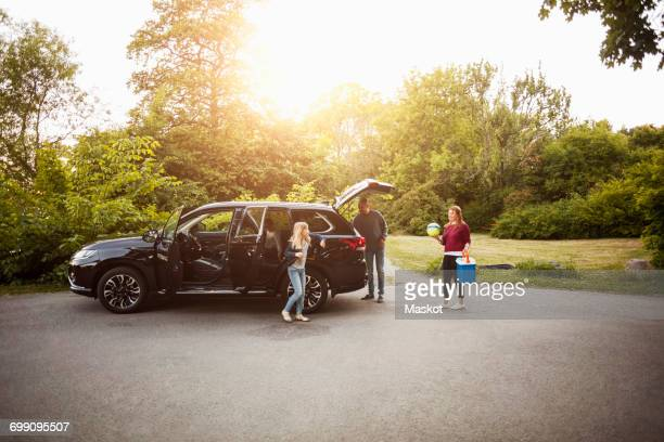 Family by black electric car against trees at park