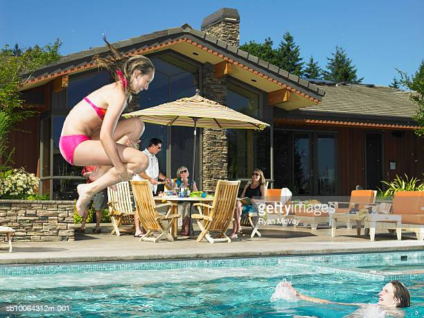 Family by pool, woman jumping in pool