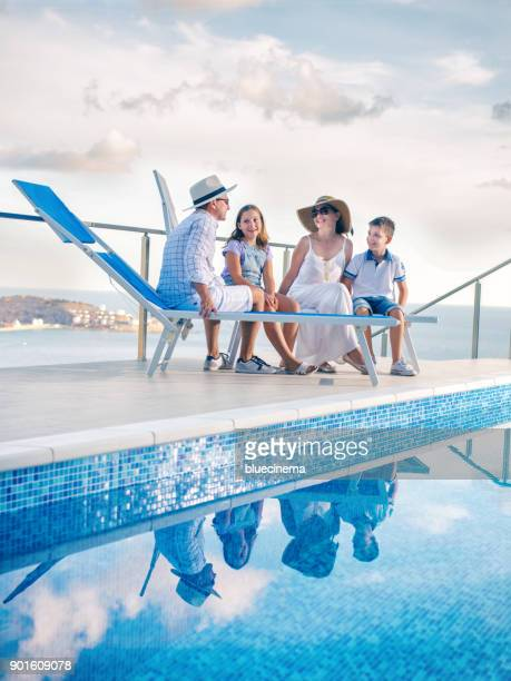 family by poolside enjoying - chaise longue stock photos and pictures