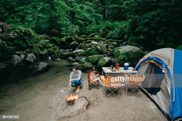 Family camping by stream in forest, Japan