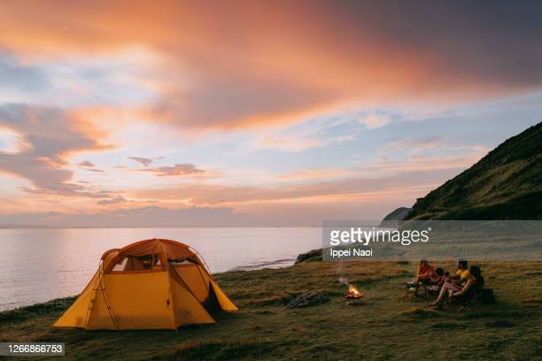 family camping by the sea at sunset - キャンプする ストックフォトと画像