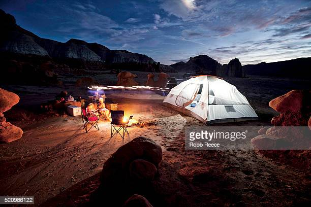 family camping in the utah desert at dusk with a camp fire and a tent - robb reece stockfoto's en -beelden