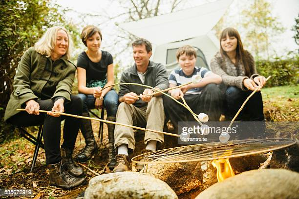 Family Camping toast marshmallows around a camp fire