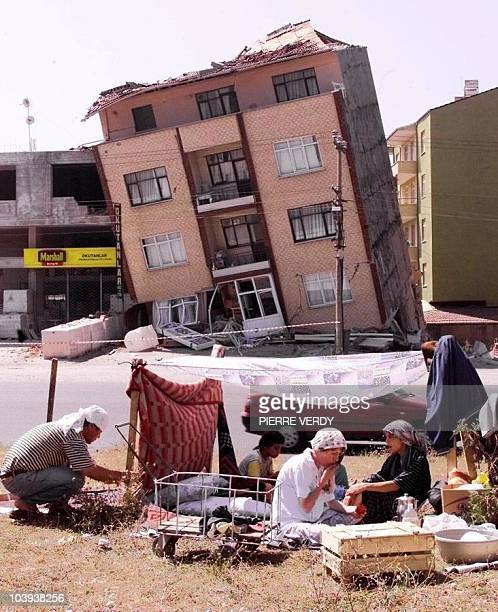 A family camps 18 August 1999 in front of a wrecked house on one of the main avenues of the town of Izmit on the Marmara Sea where the death toll...