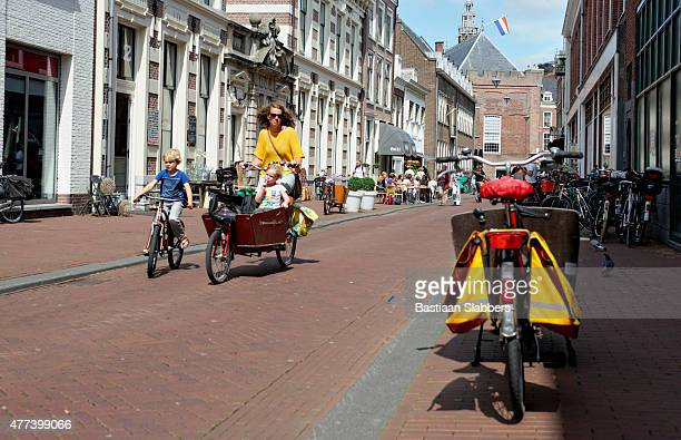 family cargo-bikes on bike designated street in commercial district - haarlem stock photos and pictures