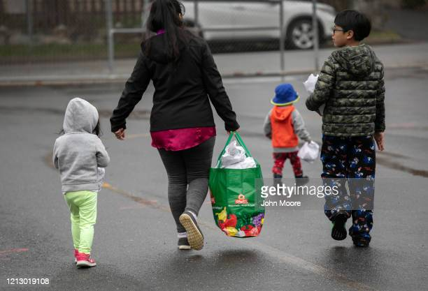 A family carries home bagged meals given out as part of Stamford Public Schools' Grab and Go Meals for Kids program which is part of the city's...