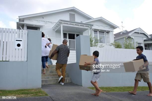 family carries moving boxes into their new home - rafael ben ari stock-fotos und bilder