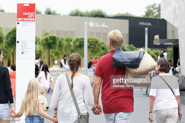A family carries shopping bags at Outletcity Metzingen on August 19 2016 in Metzingen Germany Metzingen is famous for its factory outlets attracting...