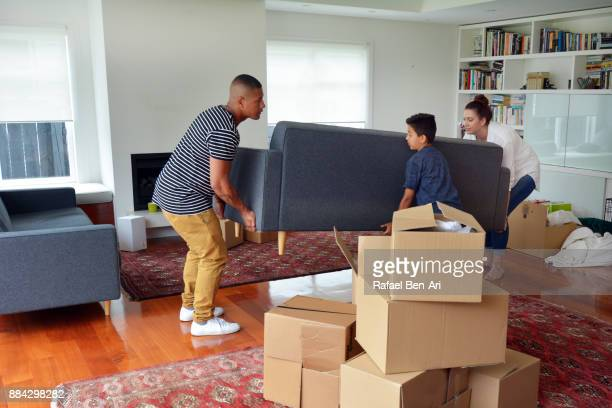 family carrying a sofa into their living room during moving into a new home - rafael ben ari stock-fotos und bilder