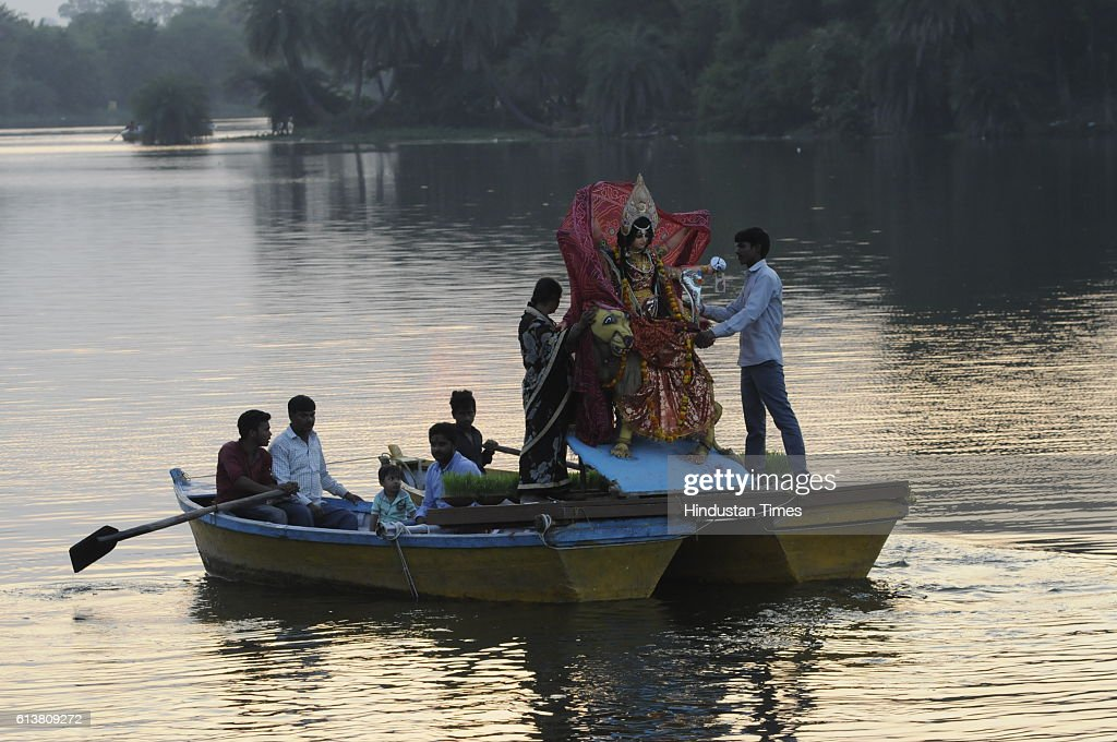 A family carrying an idol of Goddess Durga on boat for immersion at Prempura Ghat on October 10, 2016 in Bhopal, India.