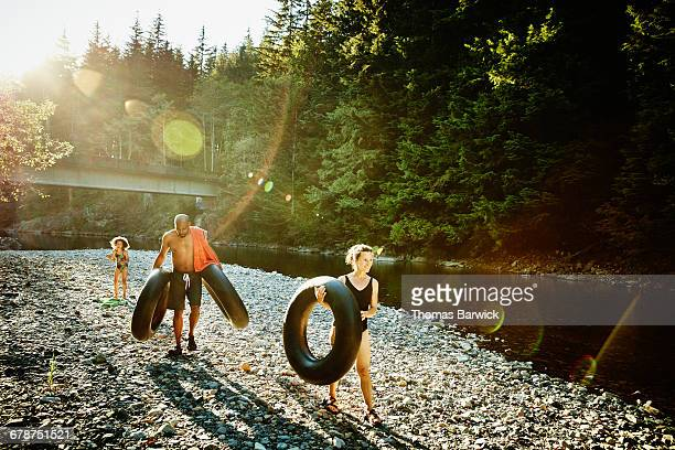 Family carrying inner tubes by river