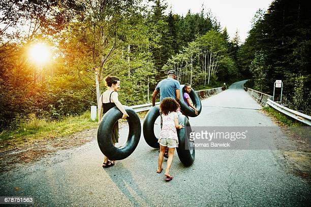 Family carrying inner tubes down road after swim